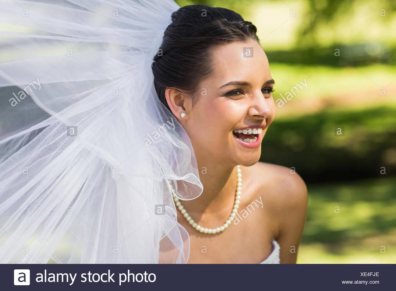 Fröhliche junge schöne Braut im park Stockbild