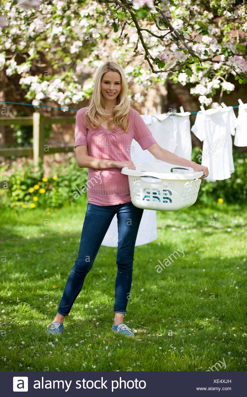 Eine junge Frau hält einen Waschkorb vor einer Wäscheleine Stockbild