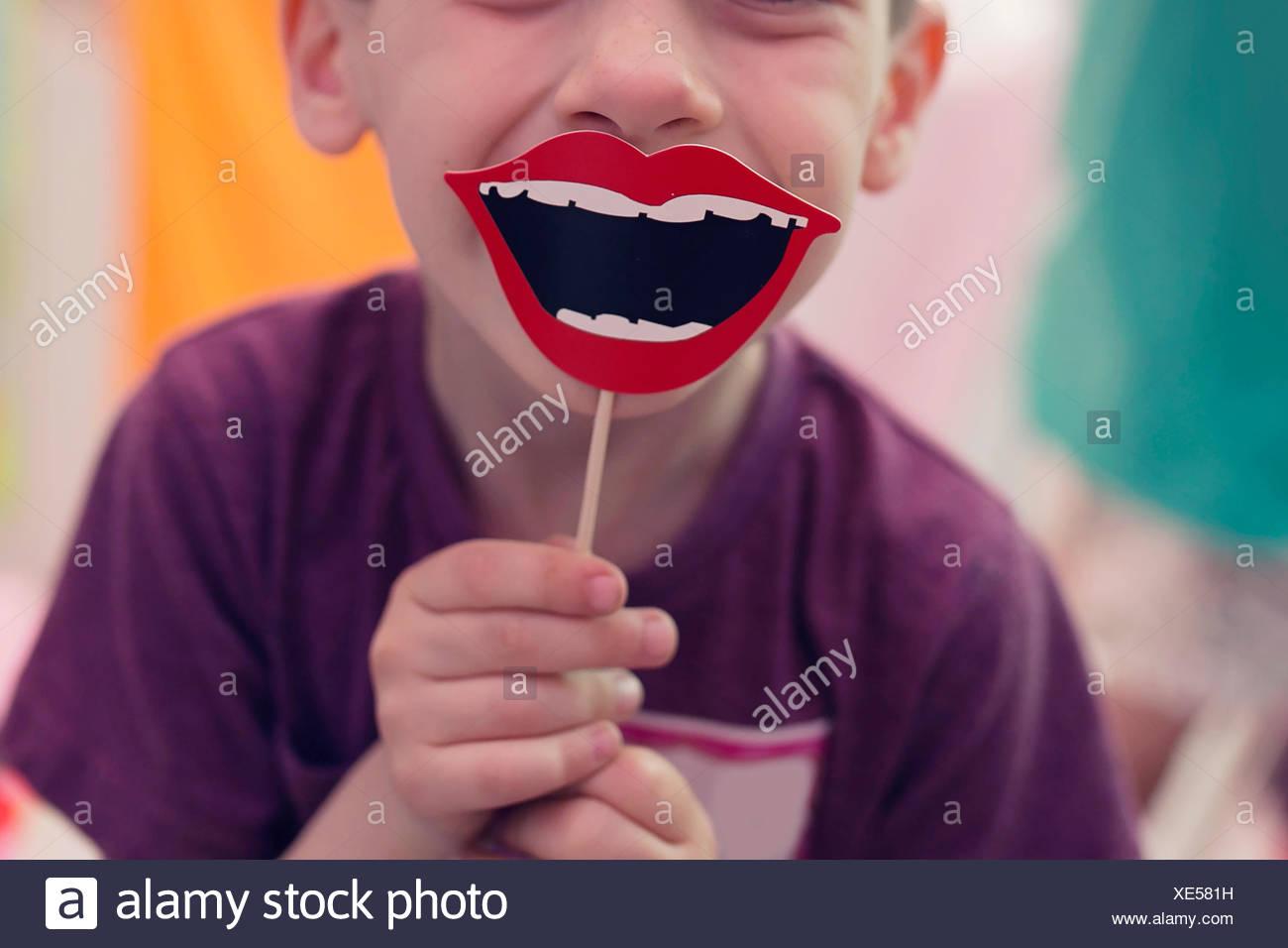 Junge hält eine Lächeln Prop auf einem stick Stockbild