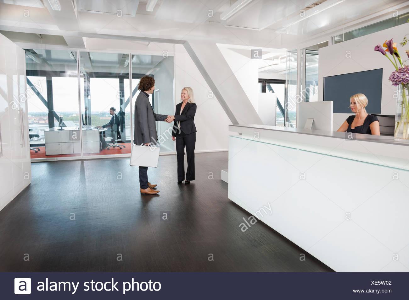 Frau Händeschütteln mit Besucher an der Rezeption Stockbild