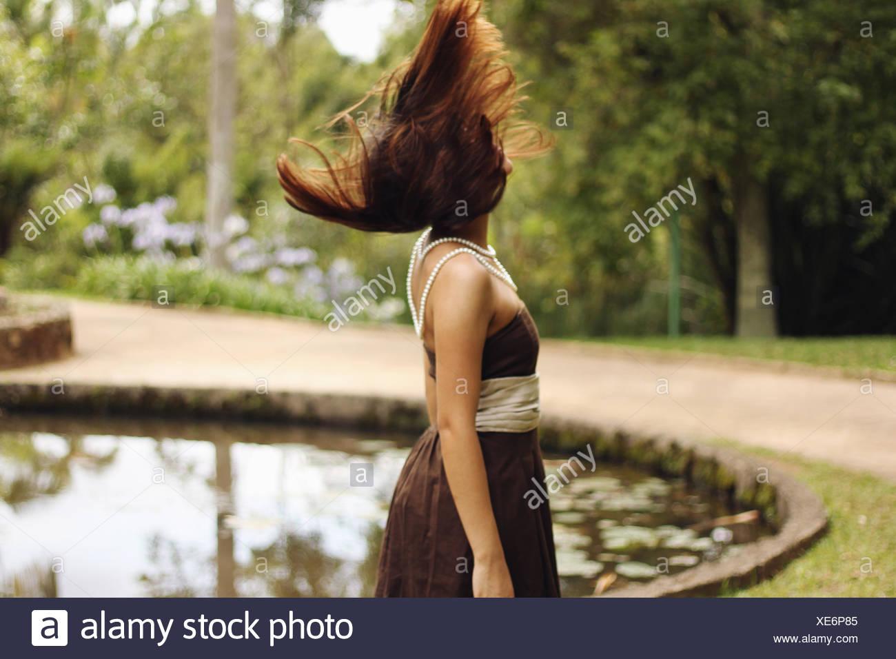 Seitenansicht einer Frau mit geblasen braunen Haaren Landschaft See Stockbild