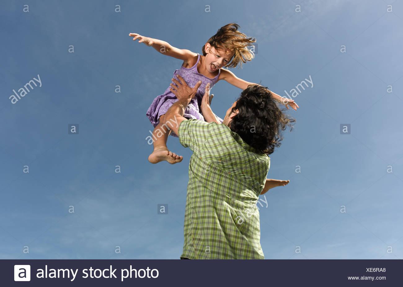 Ein Vater seine Tochter in die Luft werfen Stockbild
