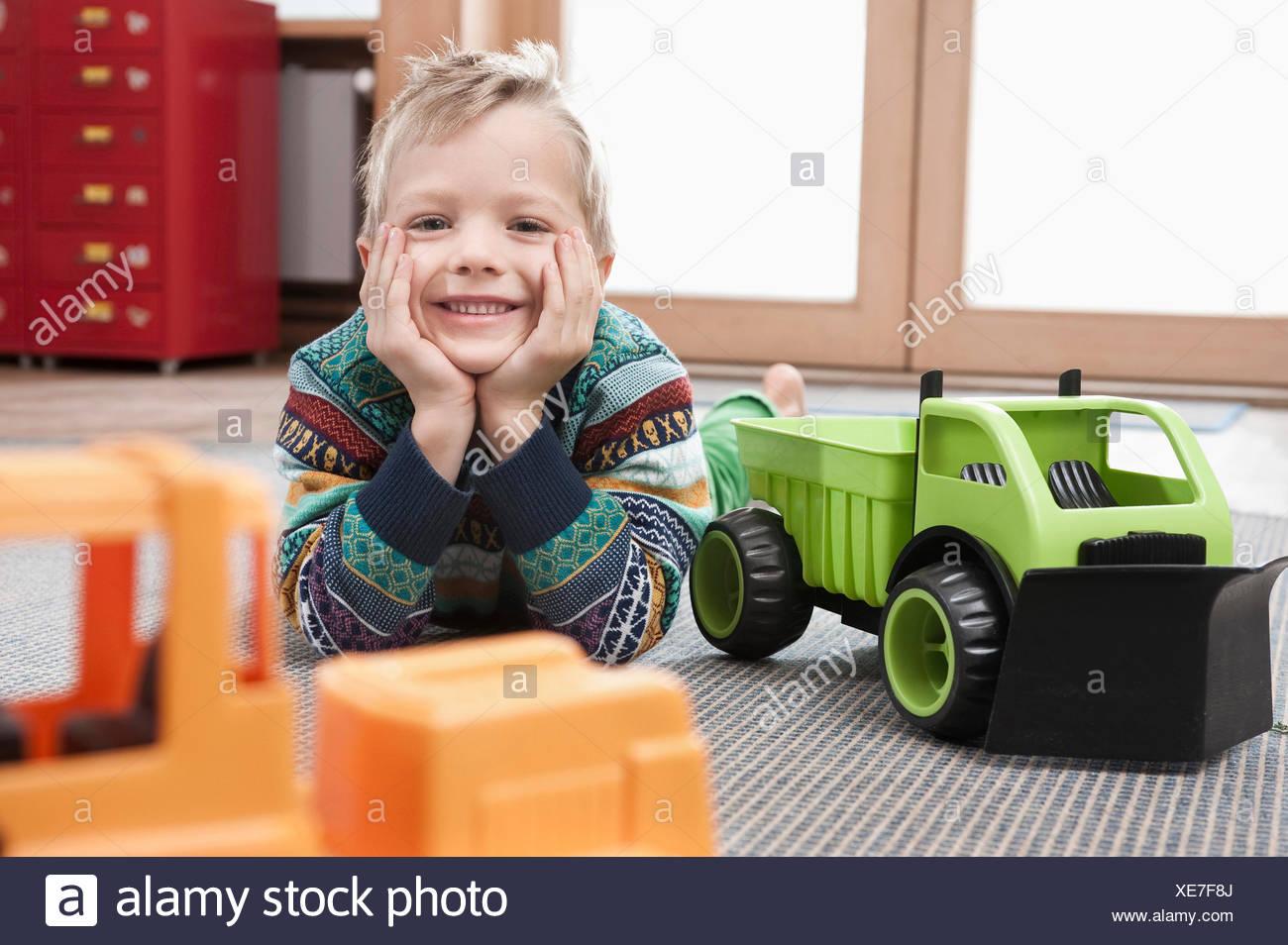 Porträt der lächelnde Knabe mit Kopf in seine Hände auf Boden von seinem kindergarten Stockbild