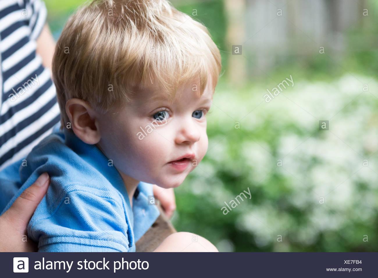 Junge sitzt auf Mutters Schoß Stockbild