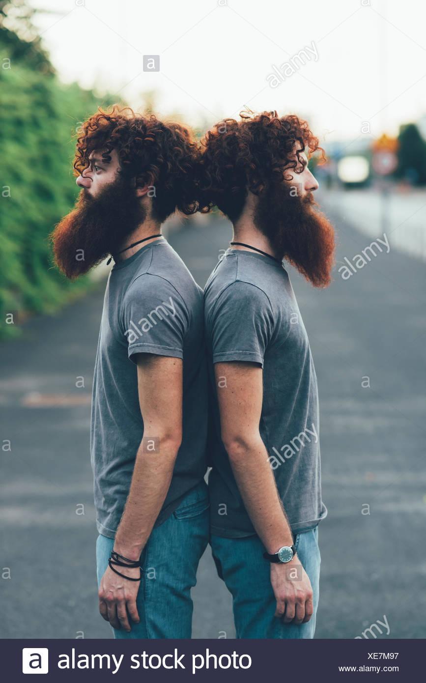 Porträt von identisch Erwachsene männliche Zwillinge mit dem roten Haar und Bärte Rücken an Rücken auf Bürgersteig Stockbild