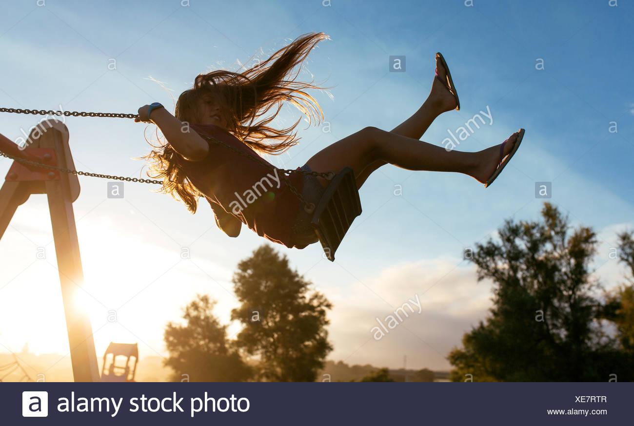 Mädchen mit Haar weht, auf einer Schaukel im Gegenlicht Stockbild