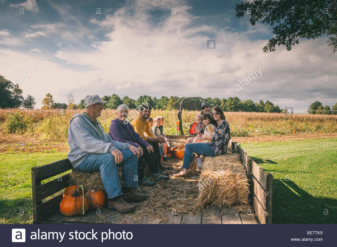 Multi-Generationen-Familie sitzt in einem Wagen an einem Kürbisfeld Stockbild