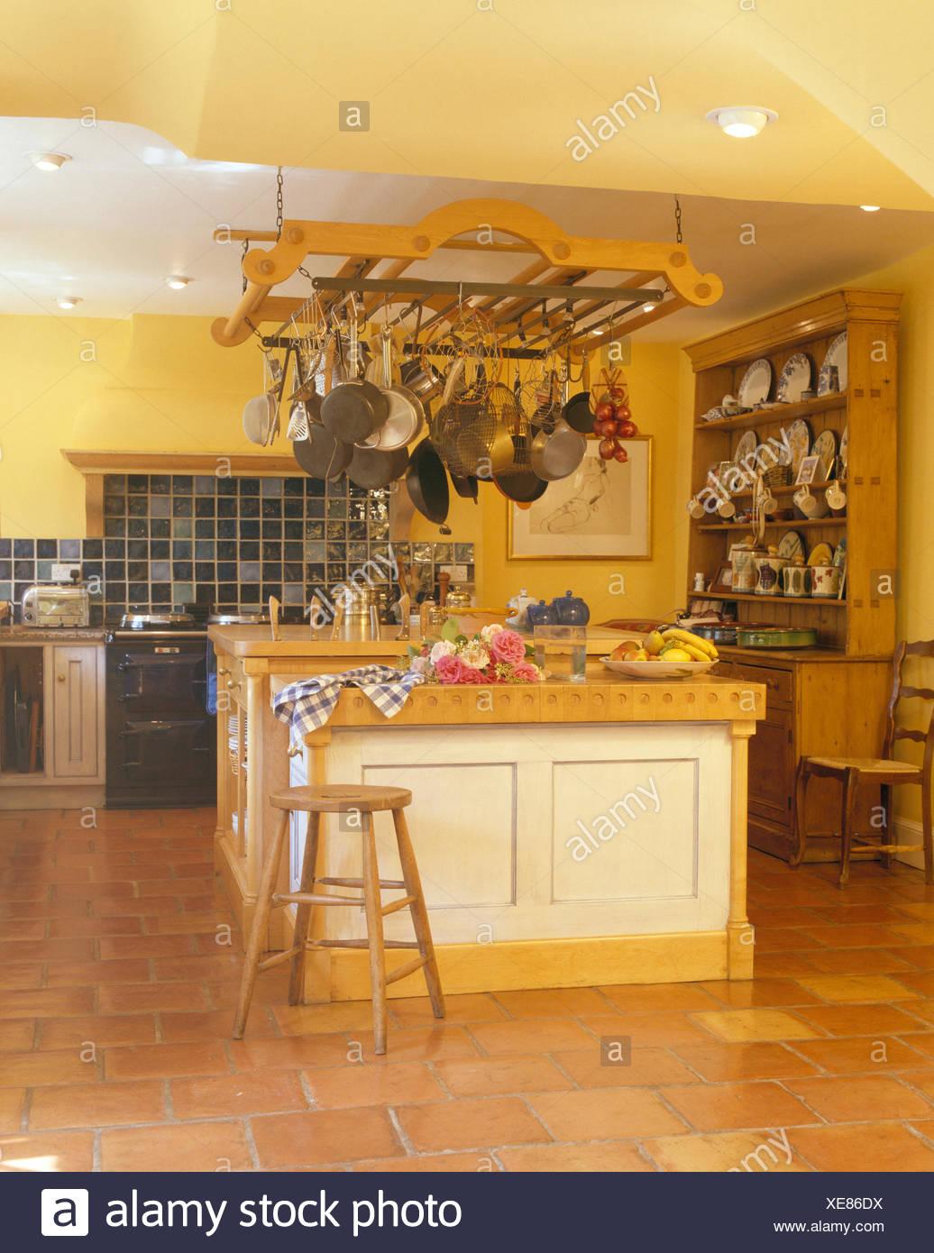 Hängenden Topf Rack über Insel Einheit in gelbe Küche mit Terrakotta ...
