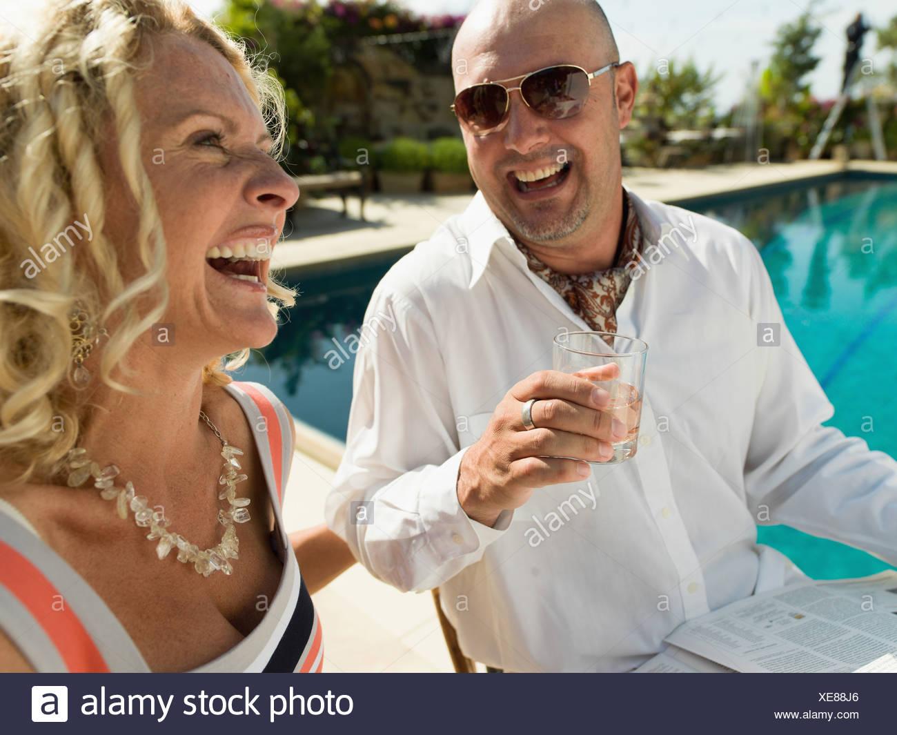 Ein junger Mann genießt sein Getränk mit einer schönen Frau an der Seite eines Schwimmbades in San Diego. Stockbild