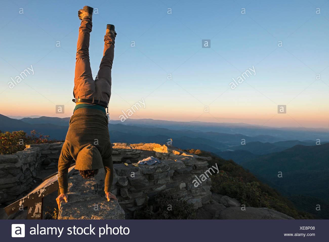 Ein Mann führt einen handstand an der Spitze der schroffen Pinnacle Wanderweg entlang des Blue Ridge Parkway. Stockbild