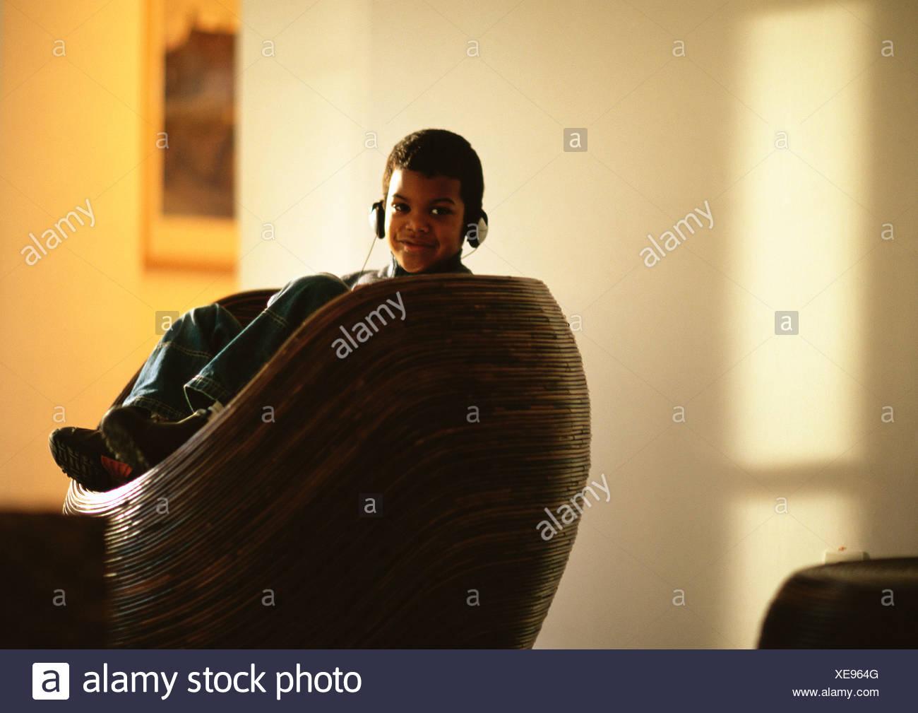 Kleiner Junge sitzt im Stuhl Musikhören mit Kopfhörer, Lächeln Stockbild