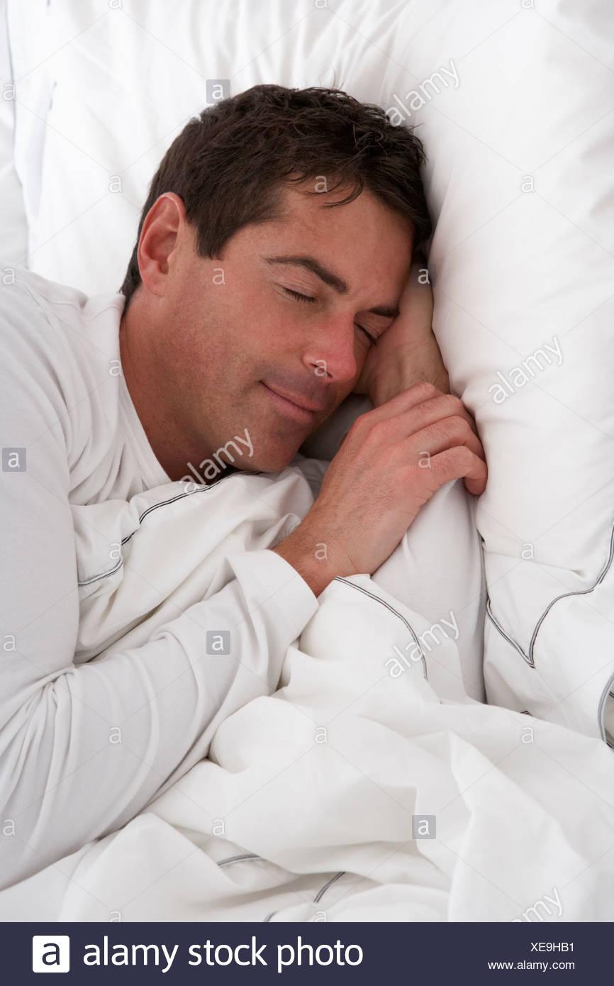Mann schläft friedlich im Bett Stockbild