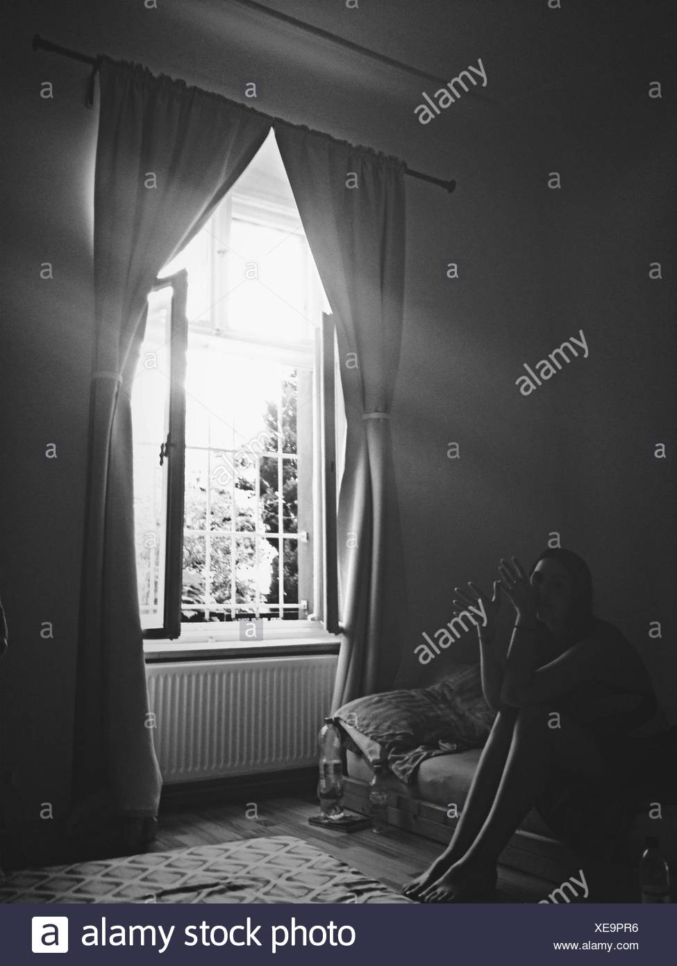 Frau sitzt im Haus Stockbild