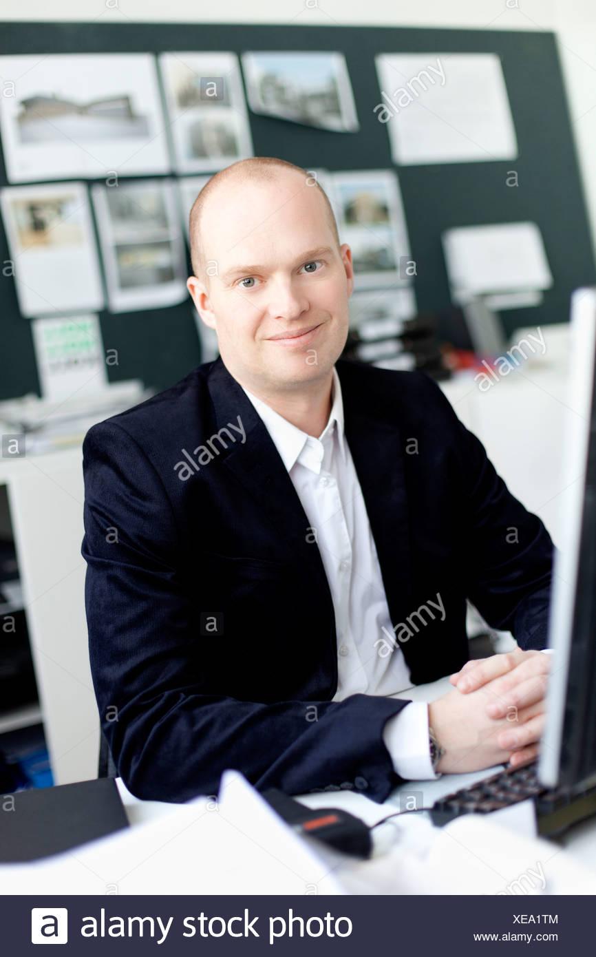 Mann sitzt im Büro, Lächeln Stockbild