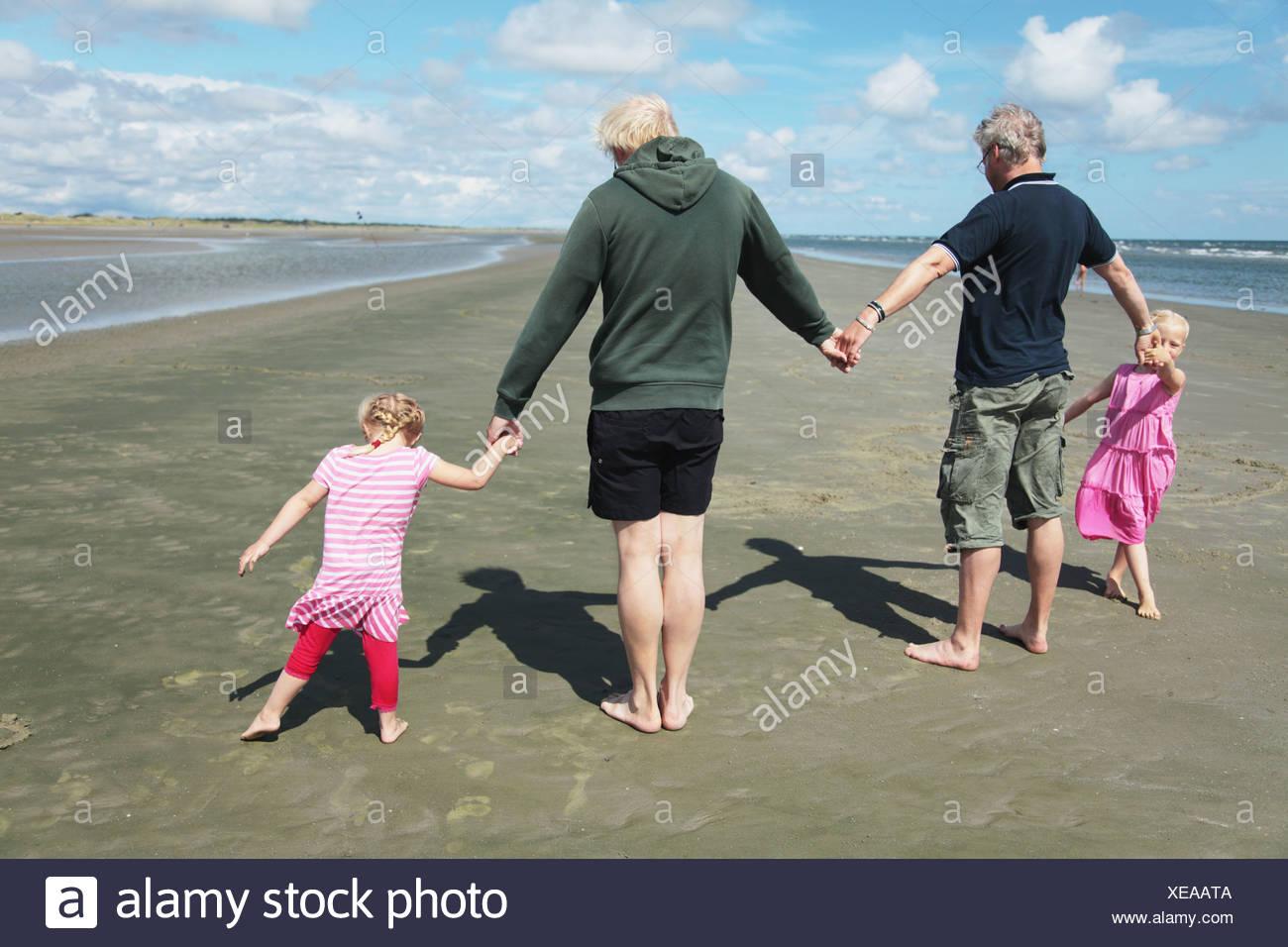 Rückansicht der Eltern und Töchter (4-7) Hand in Hand am Strand Stockbild