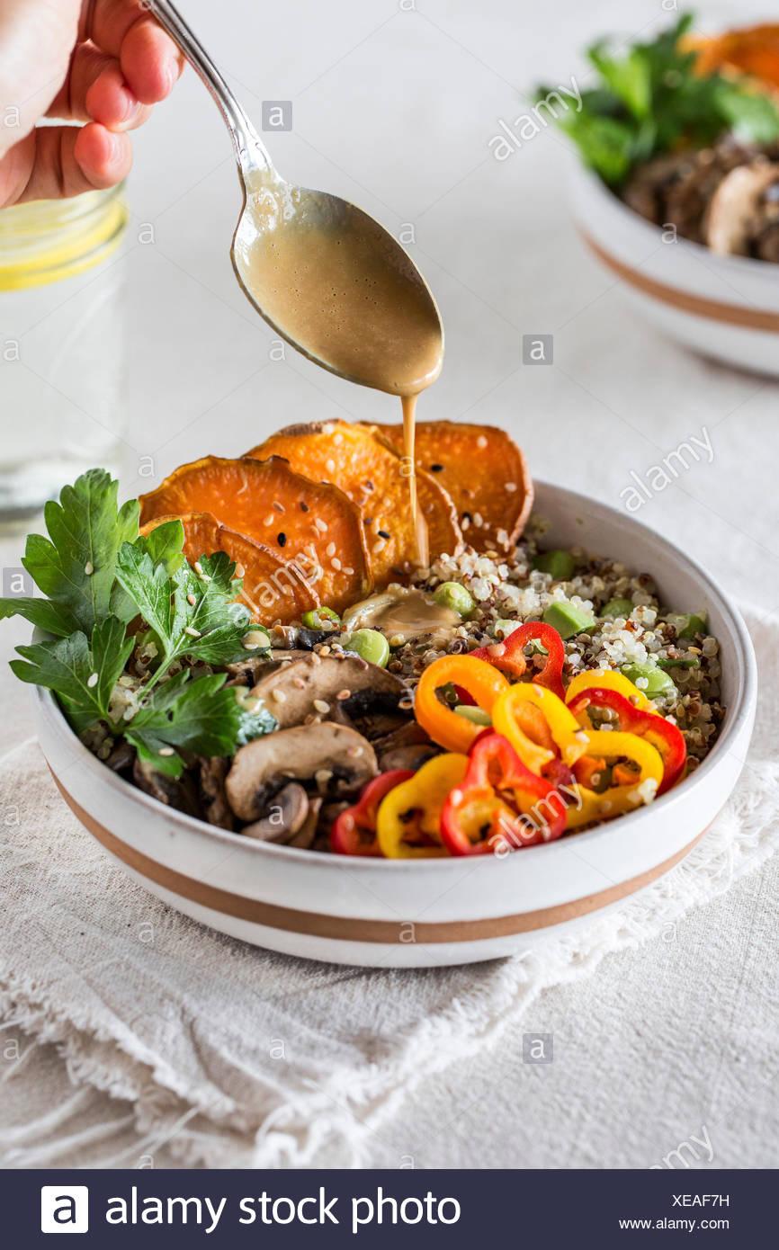 Eine Schüssel mit Quinoa garniert mit Süßkartoffeln, Pilze, Paprika und beträufelt mit Tahini-Sauce von einer Person. Stockbild