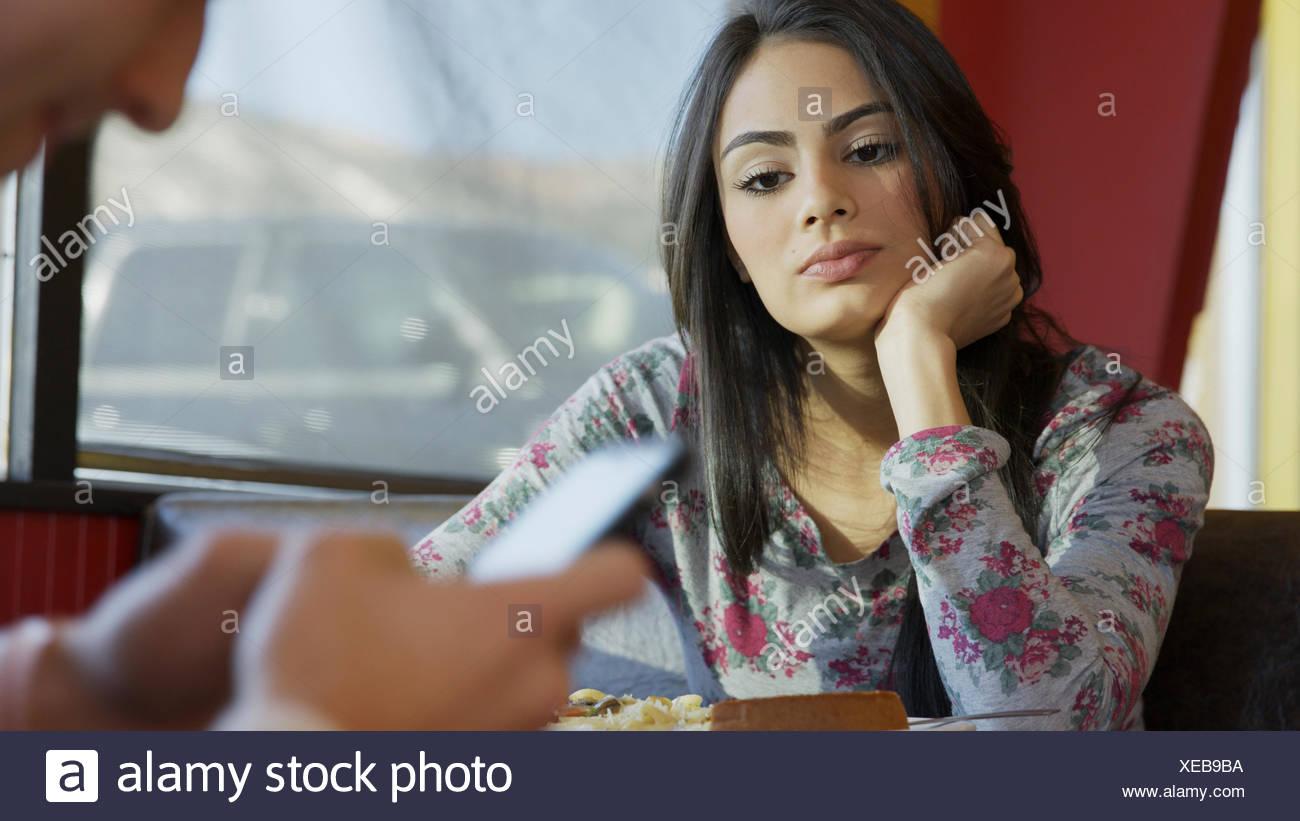 Selektiven Fokus Überblick darüber verärgert Freundin mit abgelenkt Freund mit Smartphone am Tisch im café Stockfoto