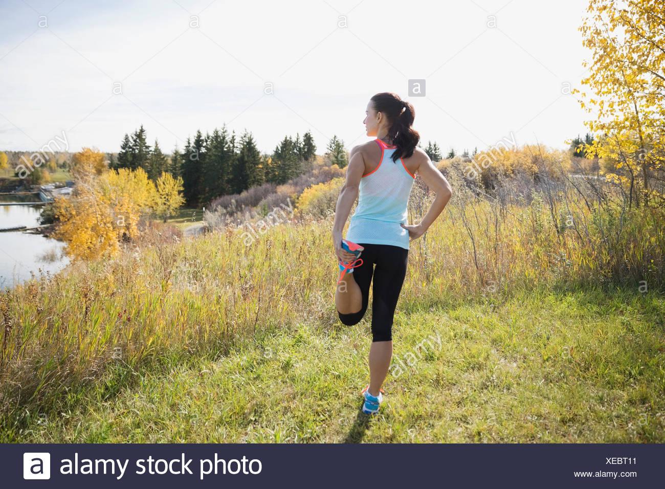 Jogger, die Dehnung Bein im Herbst Feld Stockbild