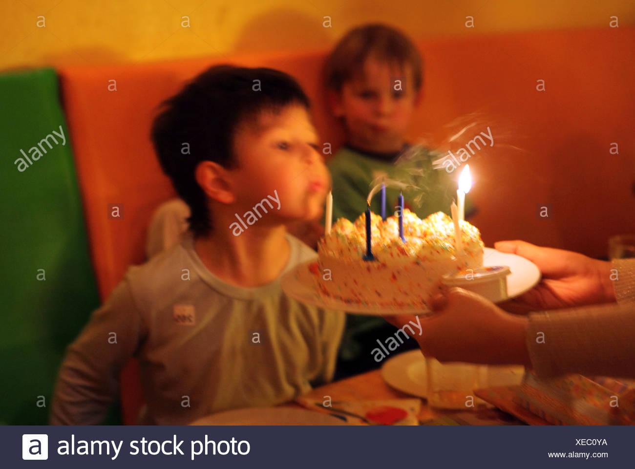 Berlin, Deutschland, junge bläst Kerzen auf der Torte Stockbild