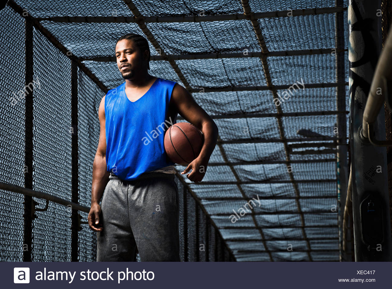 Ein junger Mann posiert mit einem Basketball auf einer Brücke. Stockbild