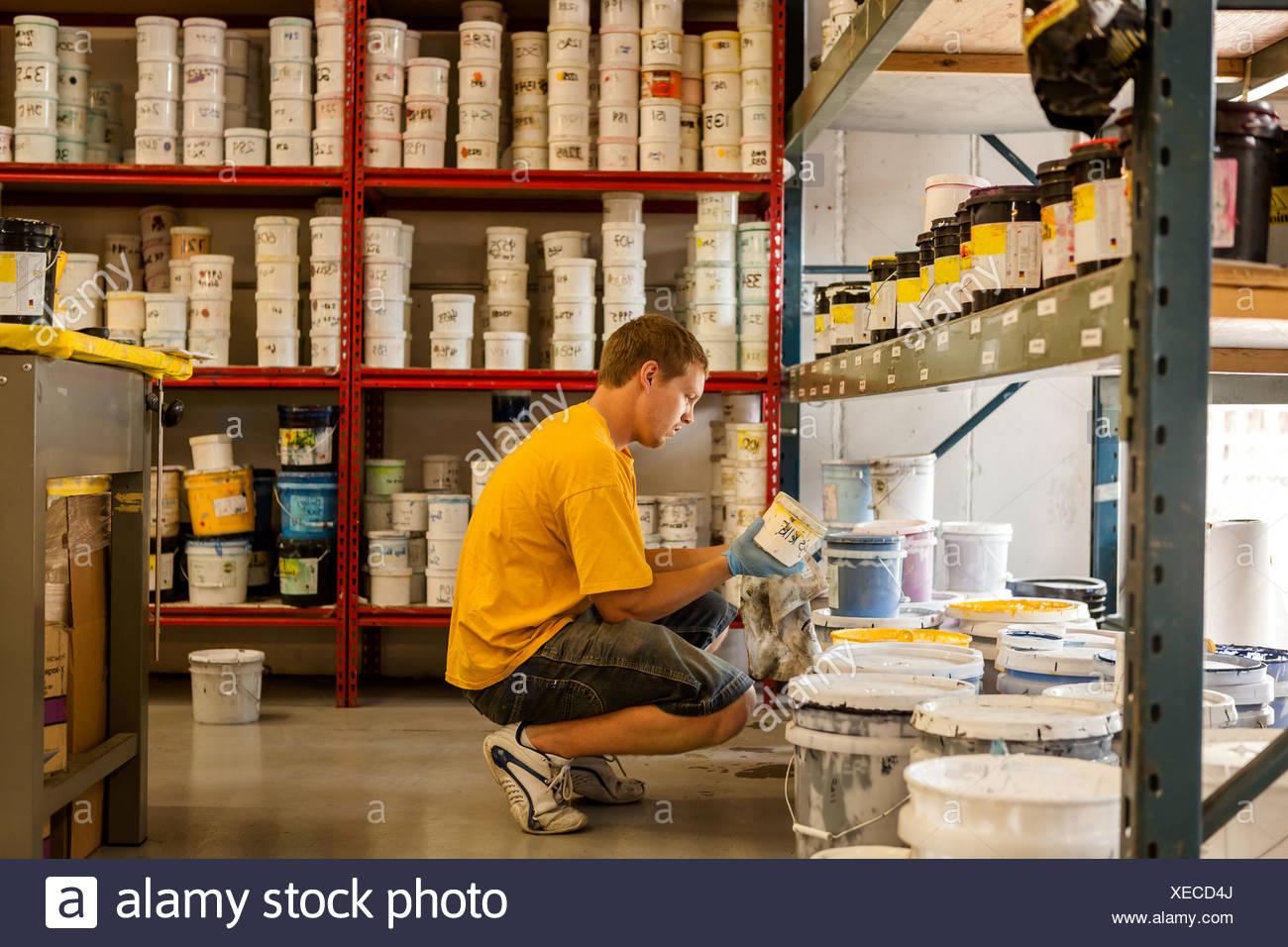 Mann auf der Suche nach Tinte in Bildschirm Druckwerkstatt Stockbild