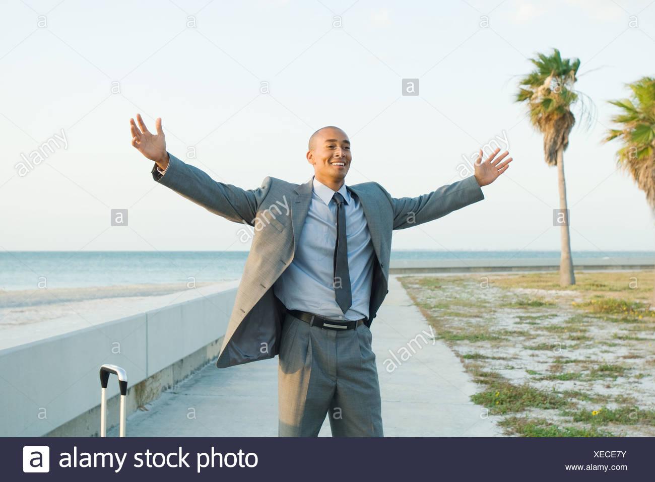 Geschäftsmann stand in der Nähe Strand mit Armen angehoben, Lächeln Stockbild