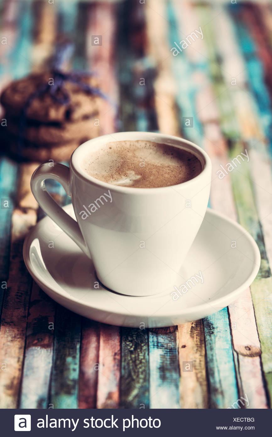 Tasse Kaffee und Schokolade Cookies auf farbigen Holz Stockbild