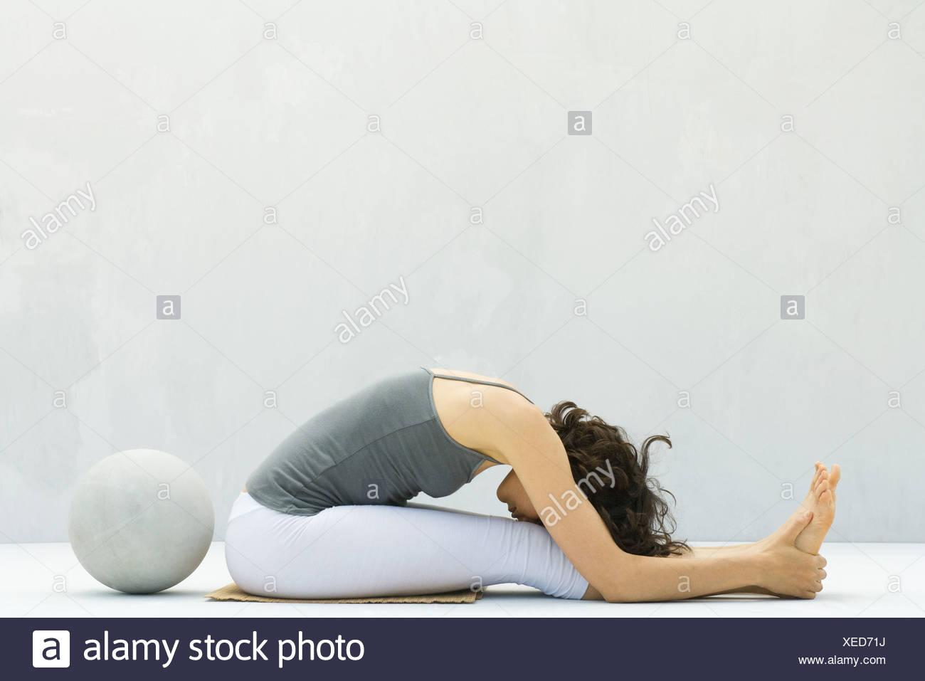 Frau sitzend, nach vorne beugen, um die Stirn zu Knien, Fitness-Ball ...