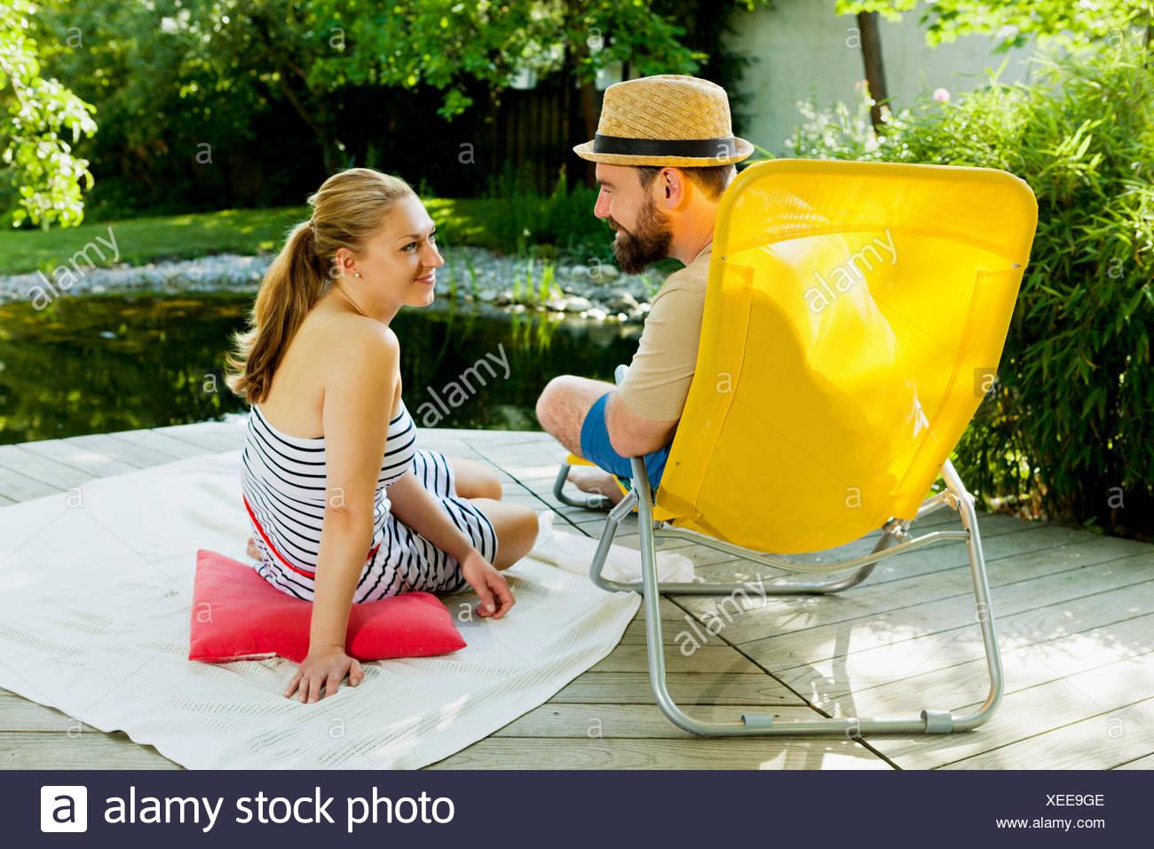 Heterosexuelles Paar nimmt sich eine Auszeit am Teich, München, Bayern, Deutschland Stockbild
