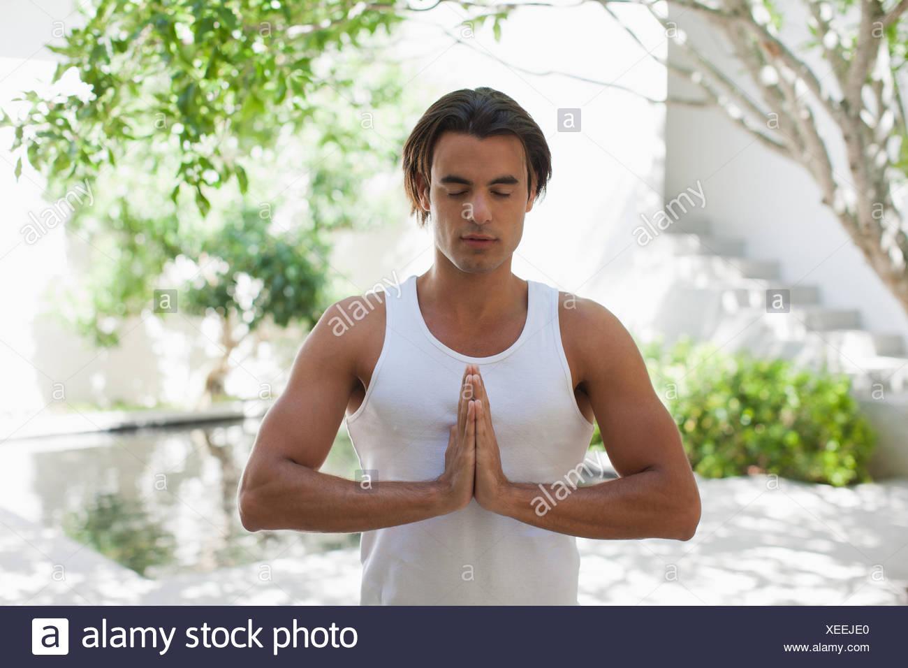Mann mit geschlossenen Augen und die Hände verschränkt auf Terrasse Stockbild