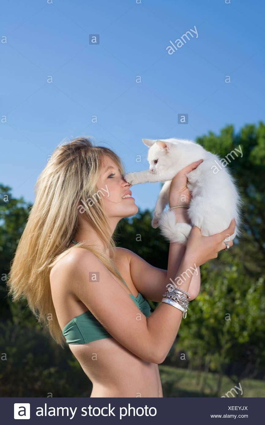 Kätzchen verleiht Pfote Teenagermädchen Nase Stockbild