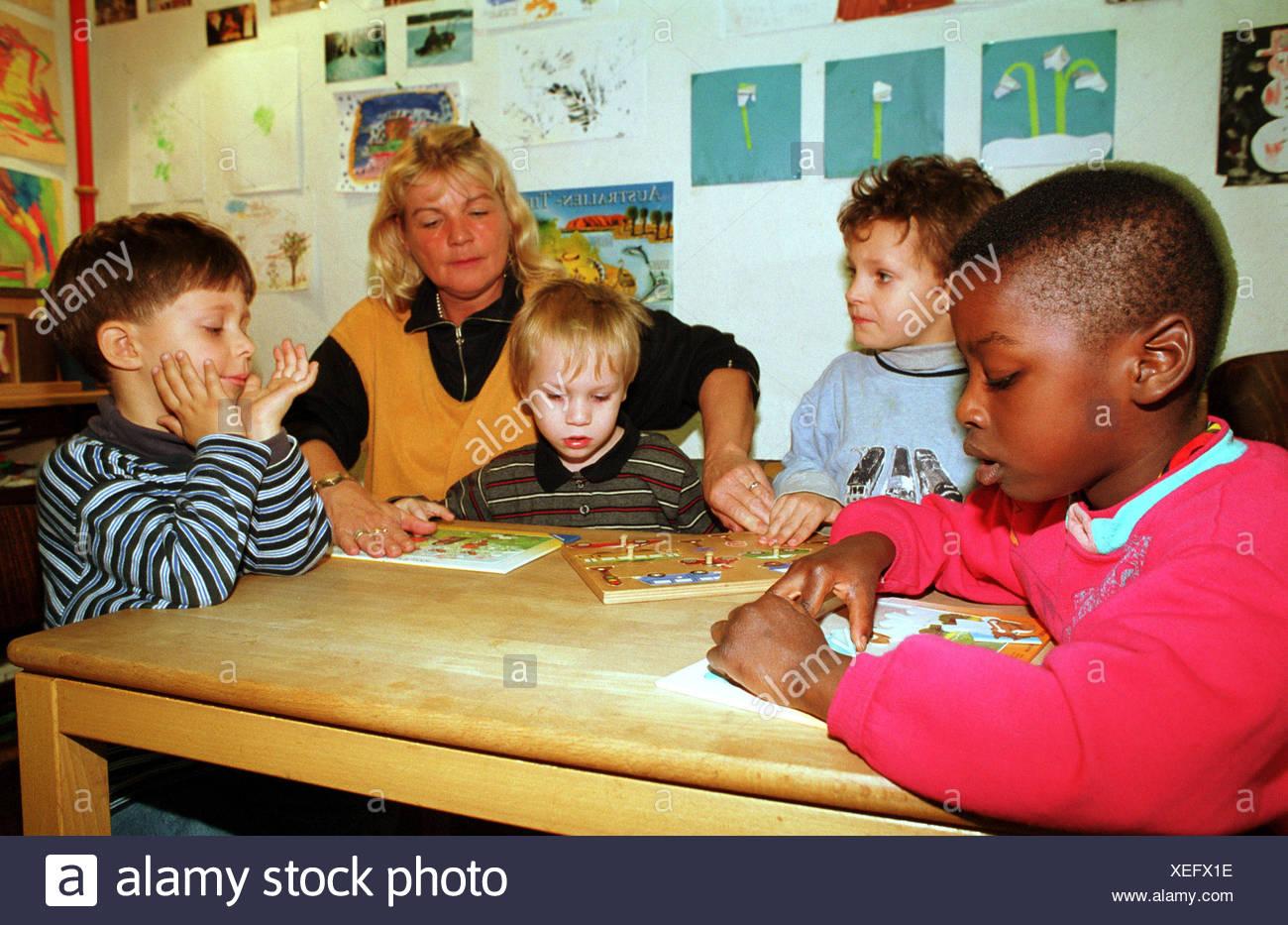 Berlin, Deutschland, Mutter mit Kindern in der Kindertagesstaette spielen Stockbild