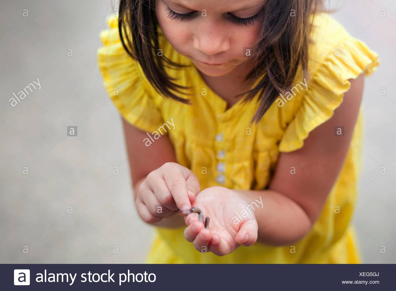 Mädchen halten und blickte auf Wurm Stockbild