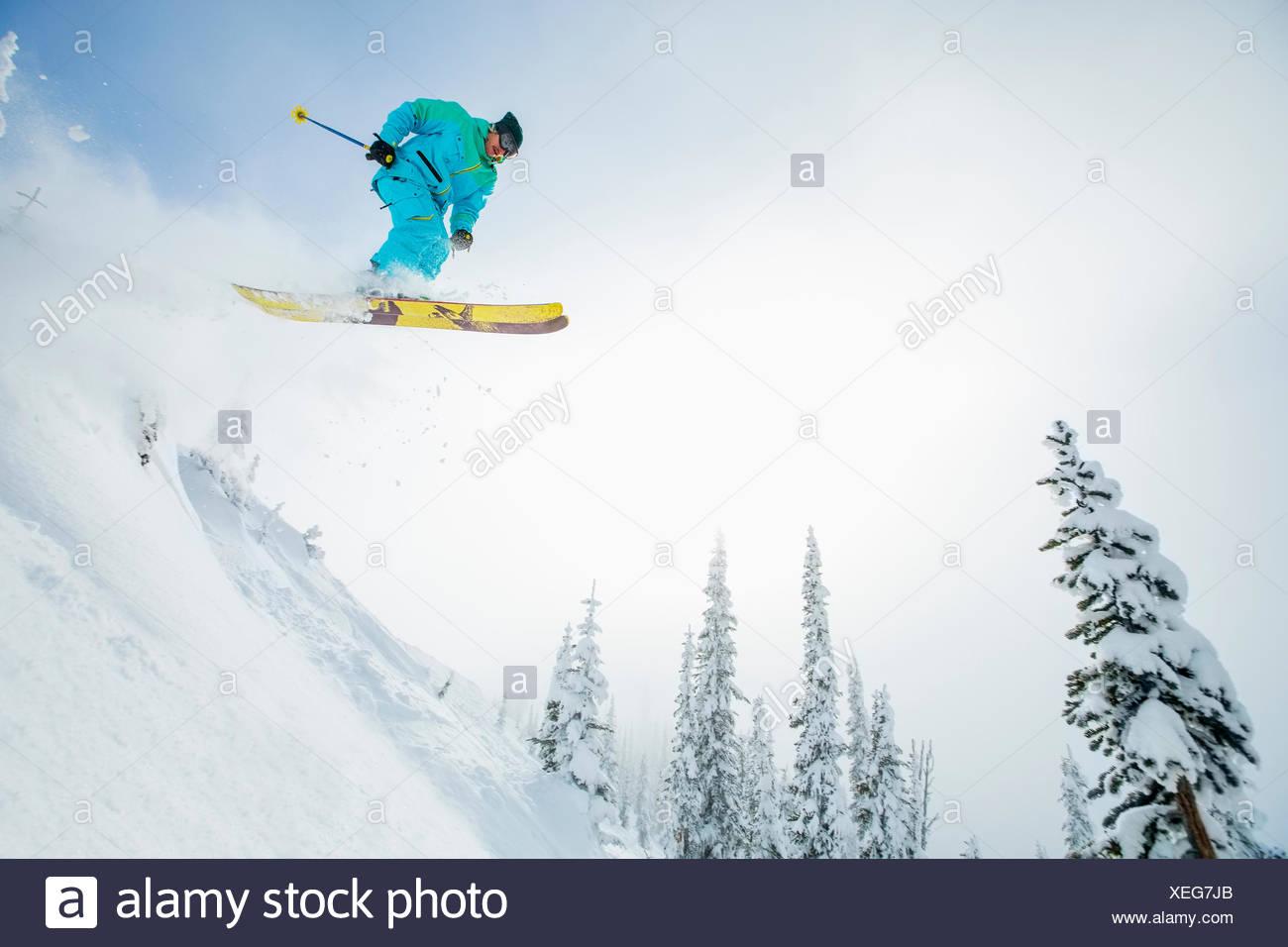 Junger Mann springt von Skipiste Stockbild