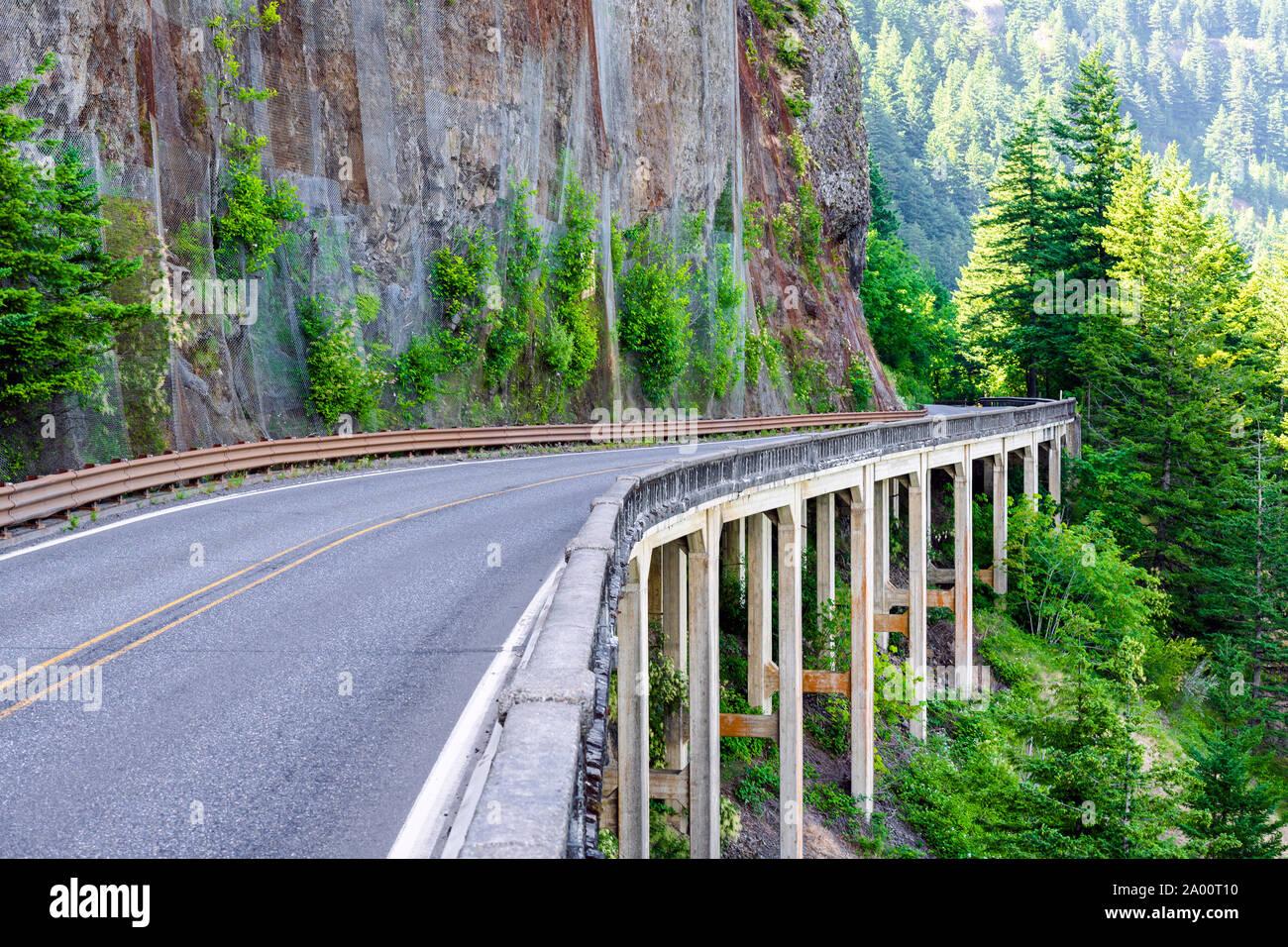 La sinuosa carretera protegida por el puente sobre el hormigón malecones alrededor de una montaña de roca en un lado y un abismo del otro lado en el espacio escénico o Foto de stock