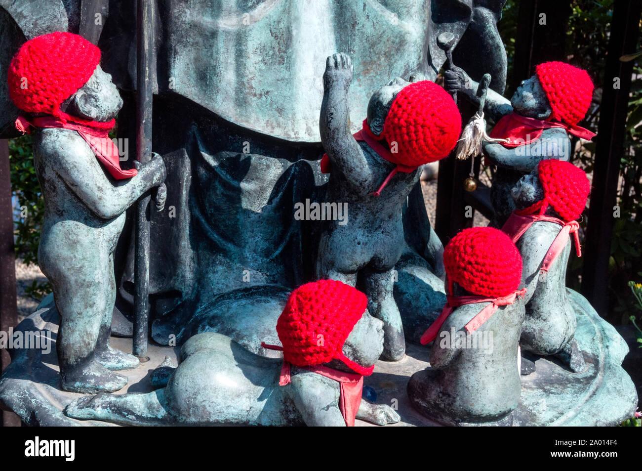 Tejido de sombreros rojos son conmovedores los regalos de los padres colocan en Jizu estatuas en honor a los niños por nacer, en Tokio, Japón. Foto de stock