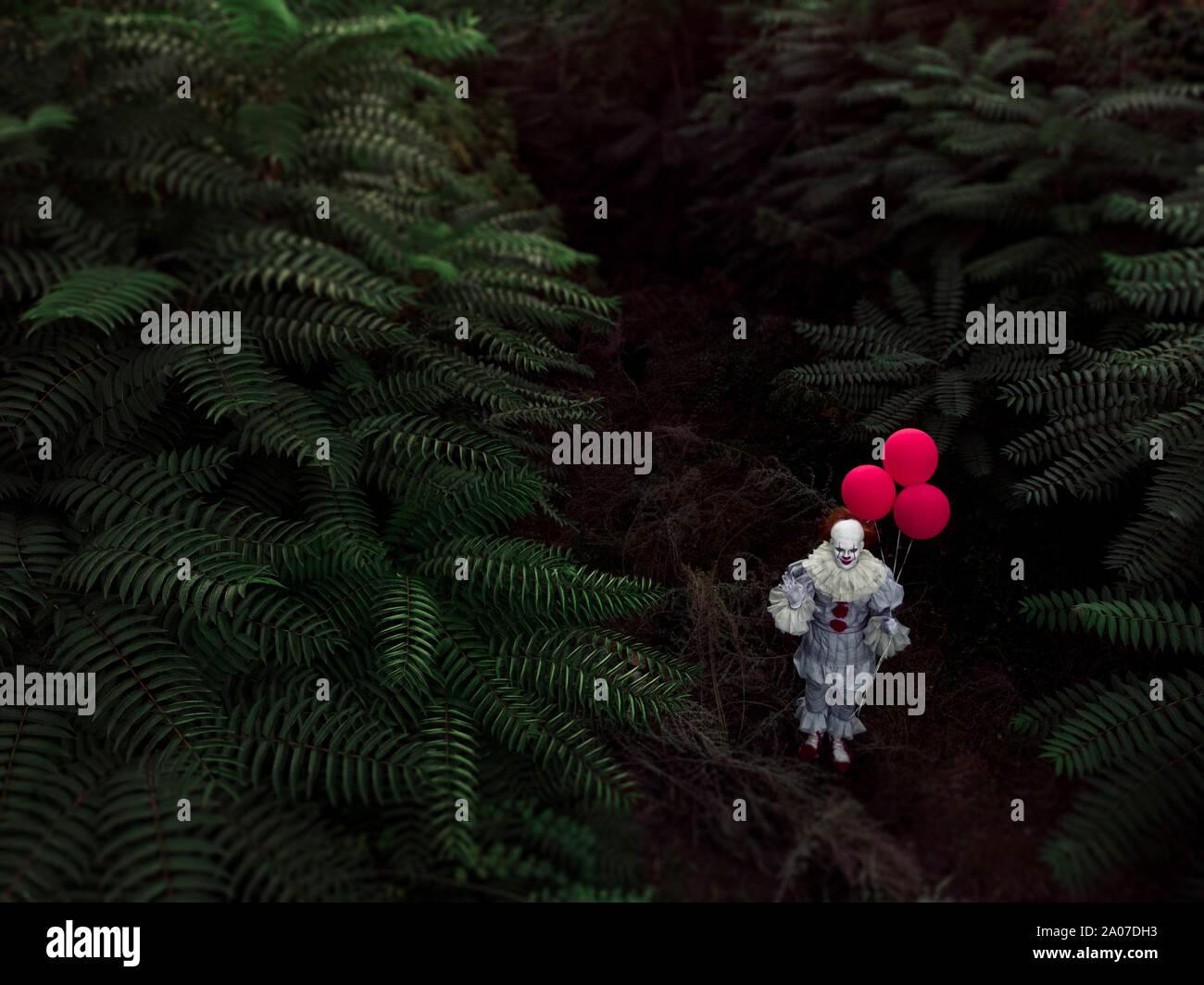 Un disparo de un Drone al hombre a la imagen de un payaso con globos rojos en su mano en el bosque. Foto de stock