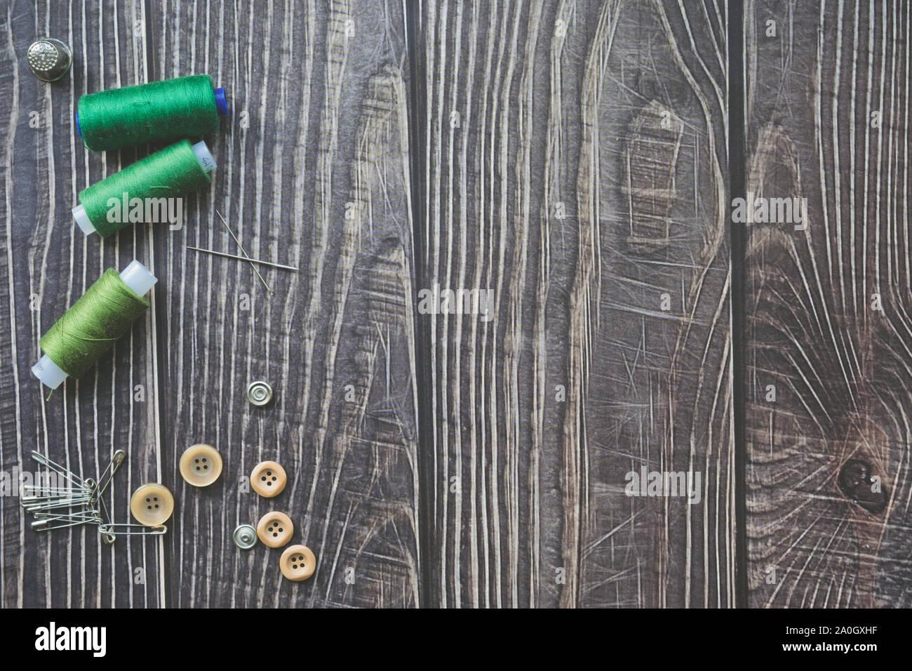 Accesorios de costura sobre fondo de madera oscura. Green hilos de costura, agujas, botones y pasadores, flatlay vista superior. Foto de stock