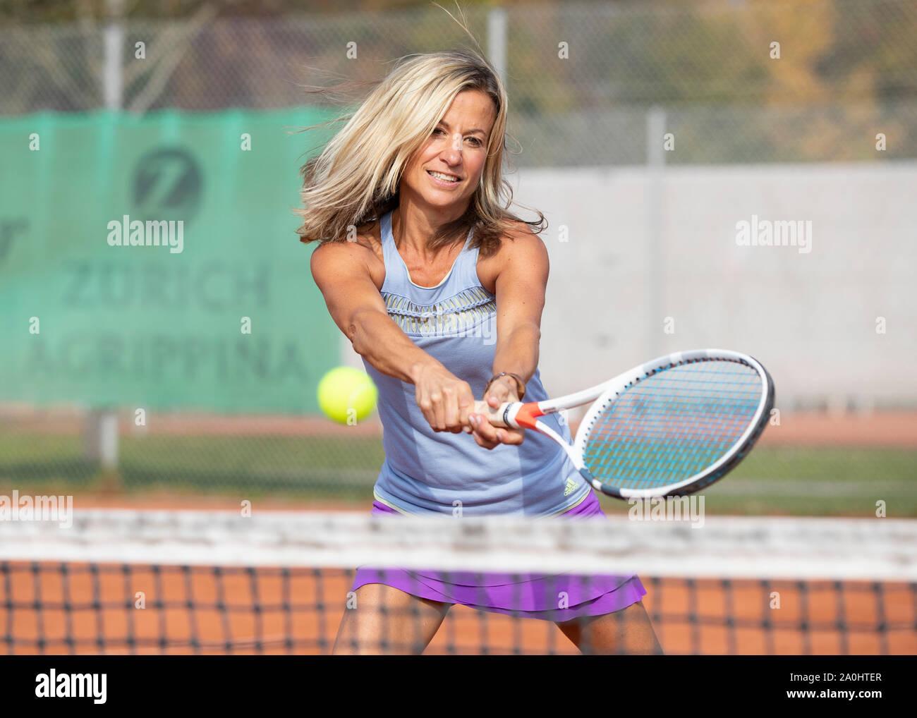 Mujer jugando al tenis golpear una volea de revés shot Foto de stock