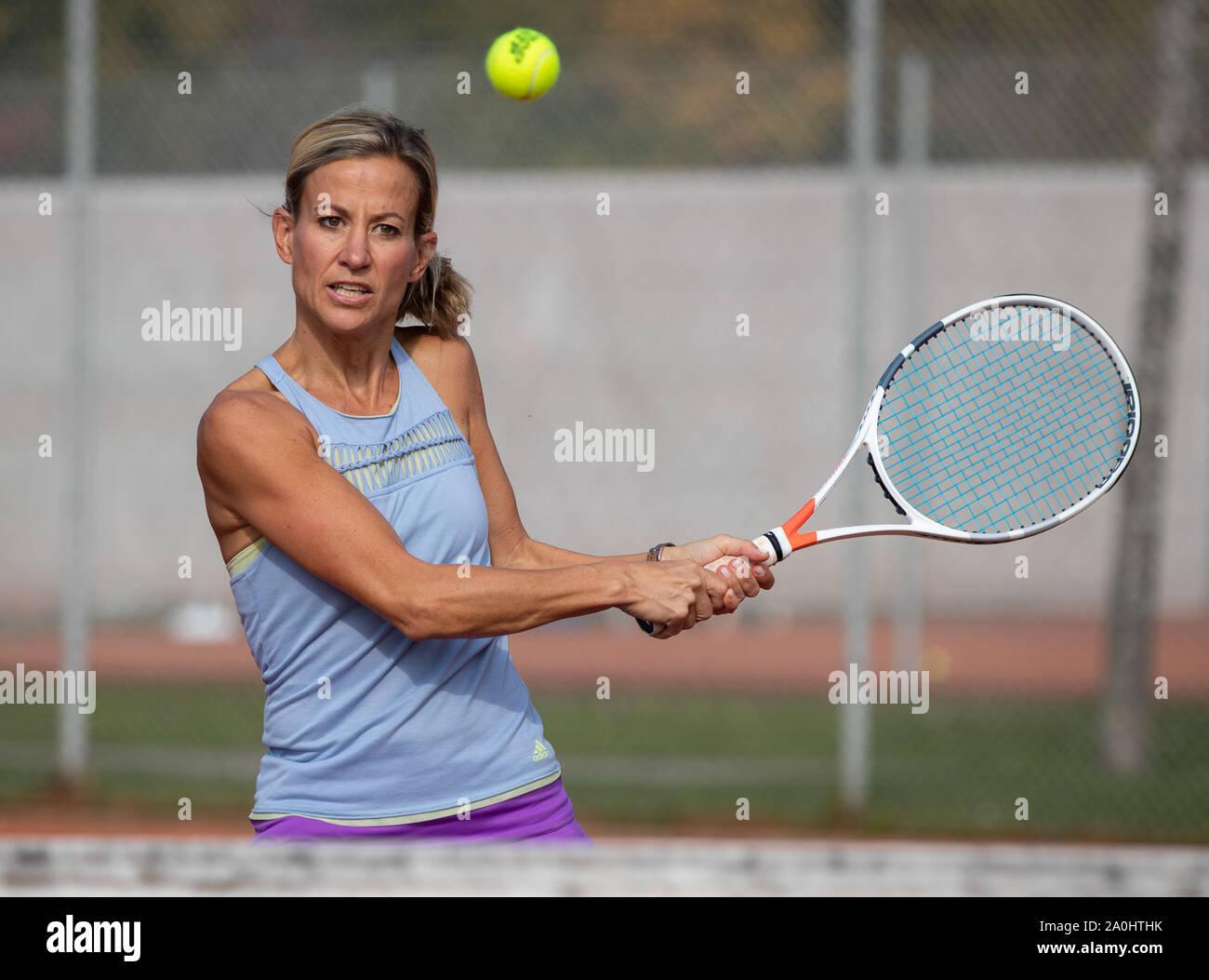 Mujer jugando al tenis golpeando un disparo de revés Foto de stock