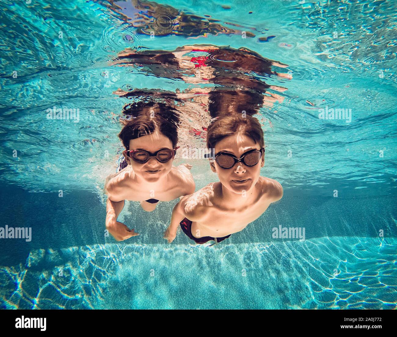 Imagen Submarina de dos niños nadando junto a otro en una piscina. Foto de stock