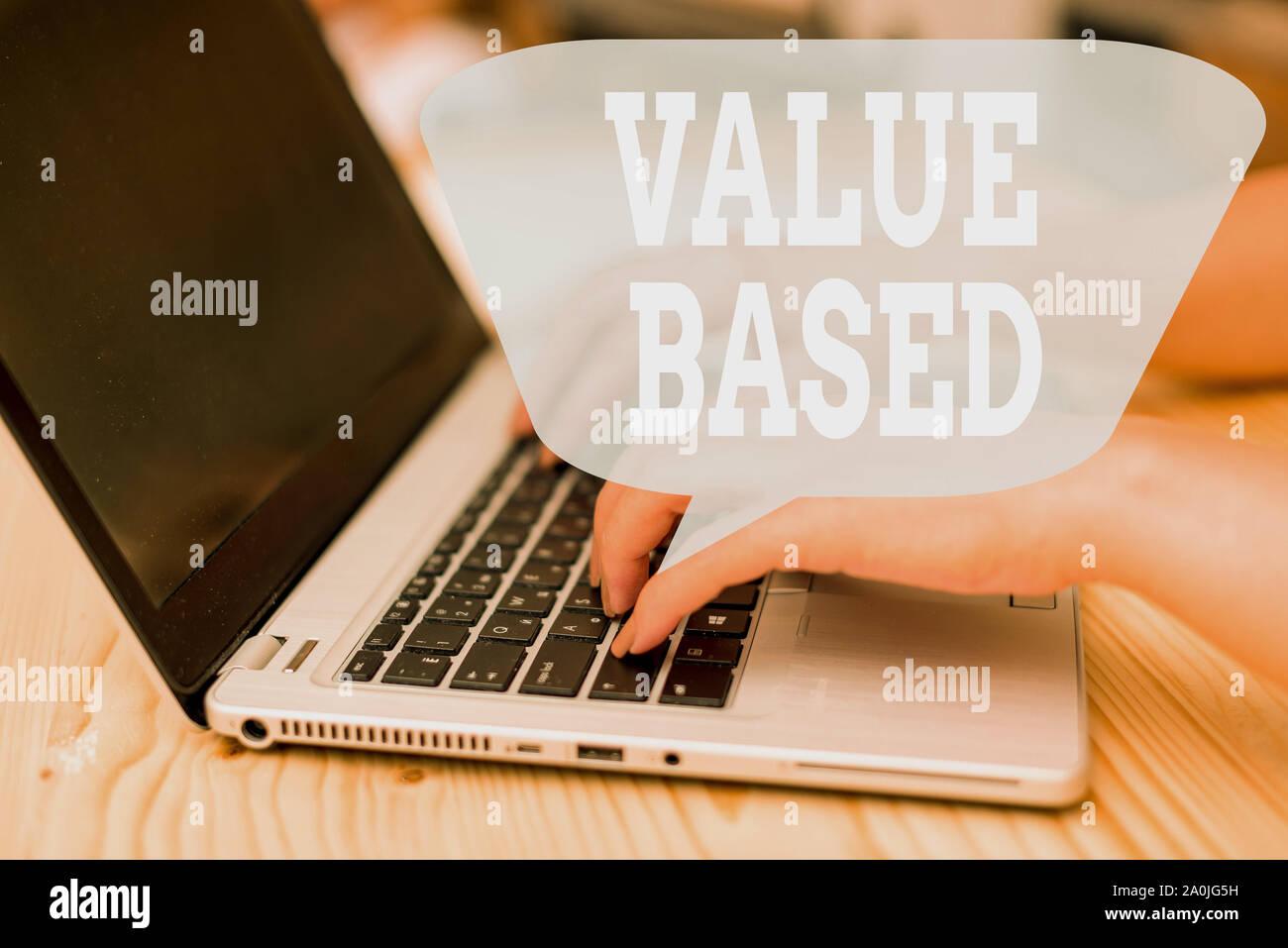 Escritura a mano conceptual mostrando valor basado. Concepto Significado considerando el producto vale la pena por la satisfacción del cliente Mujer con portátil y smartphone Foto de stock