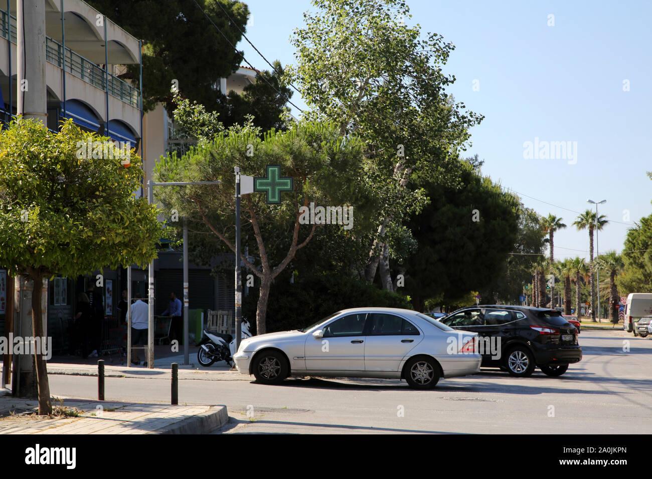 Vouliagmeni Atenas Attica Grecia autos estacionados fuera de la farmacia y el Supermercado Foto de stock
