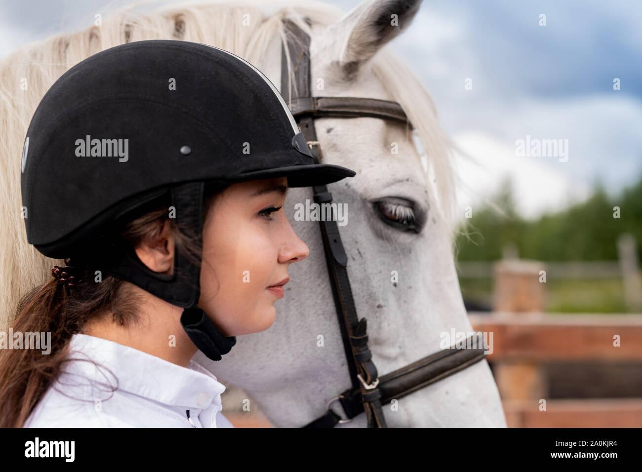 Perfil del joven mujer activa en casco y ecuestre de caballos de pura raza blanca Foto de stock