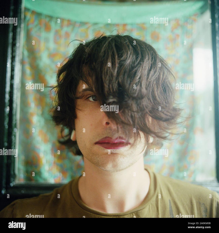 El hombre con el pelo sobre los ojos, los labios rojos Foto de stock