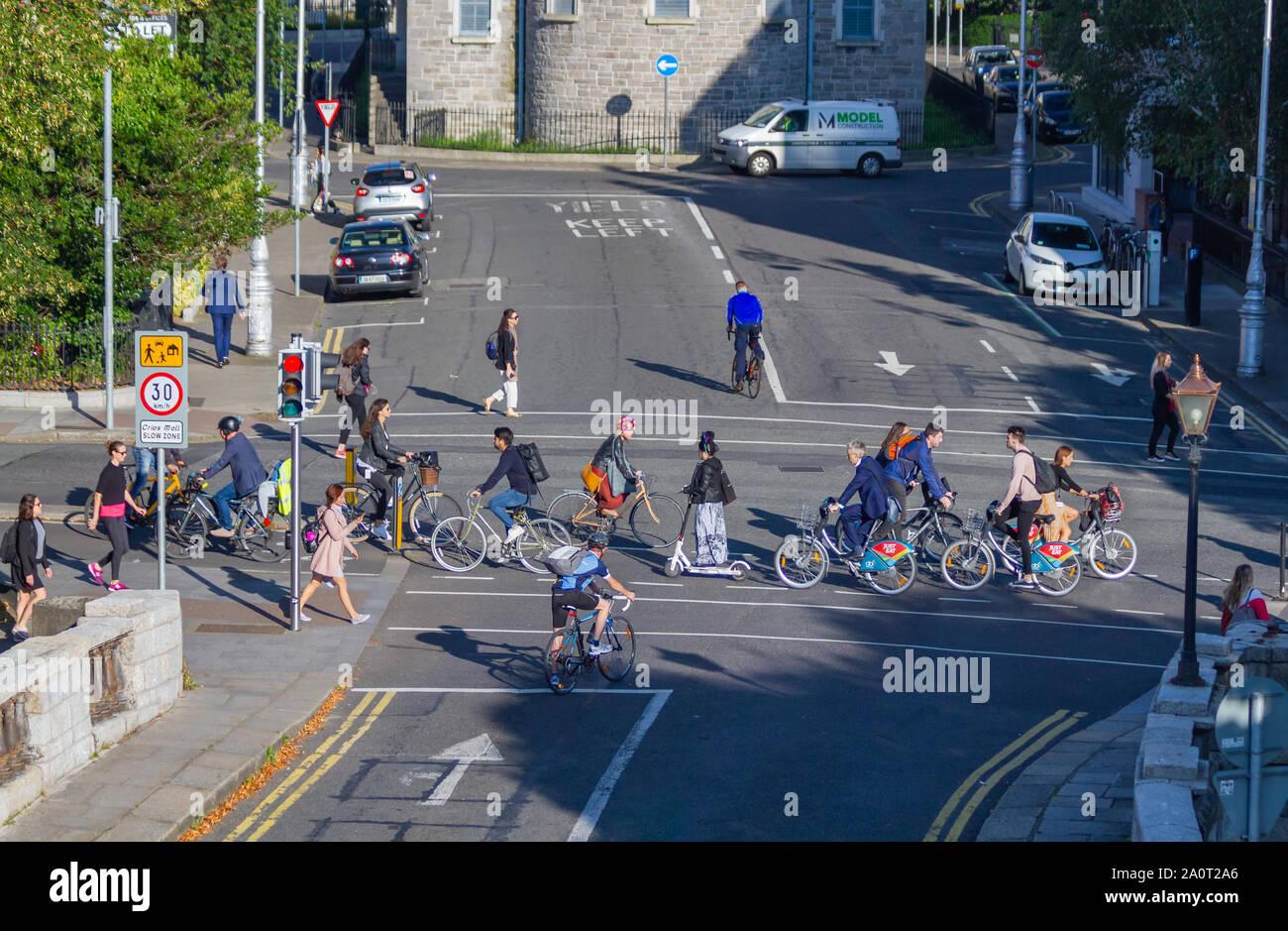 Los viajeros vienen a trabajar en bicicleta en bicicletas bicicletas, dedicada en carril bici. Persona en e scooter, coche eléctrico de carga. Dublín, Irlanda Low Carbon conmutar Foto de stock