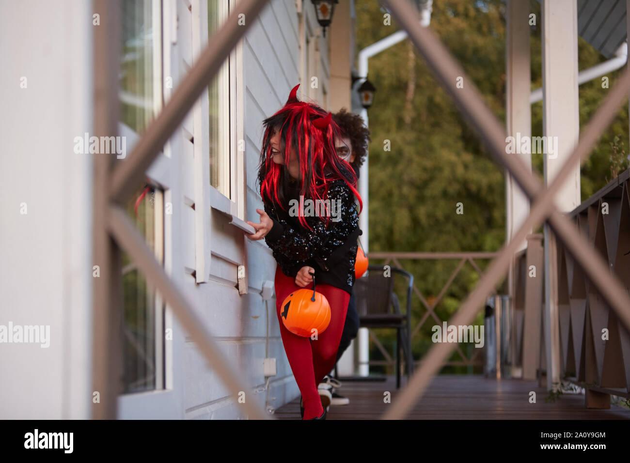 Retrato de dos niños escondidos furtivos fuera de la casa mientras estás jugando en Halloween, espacio de copia Foto de stock