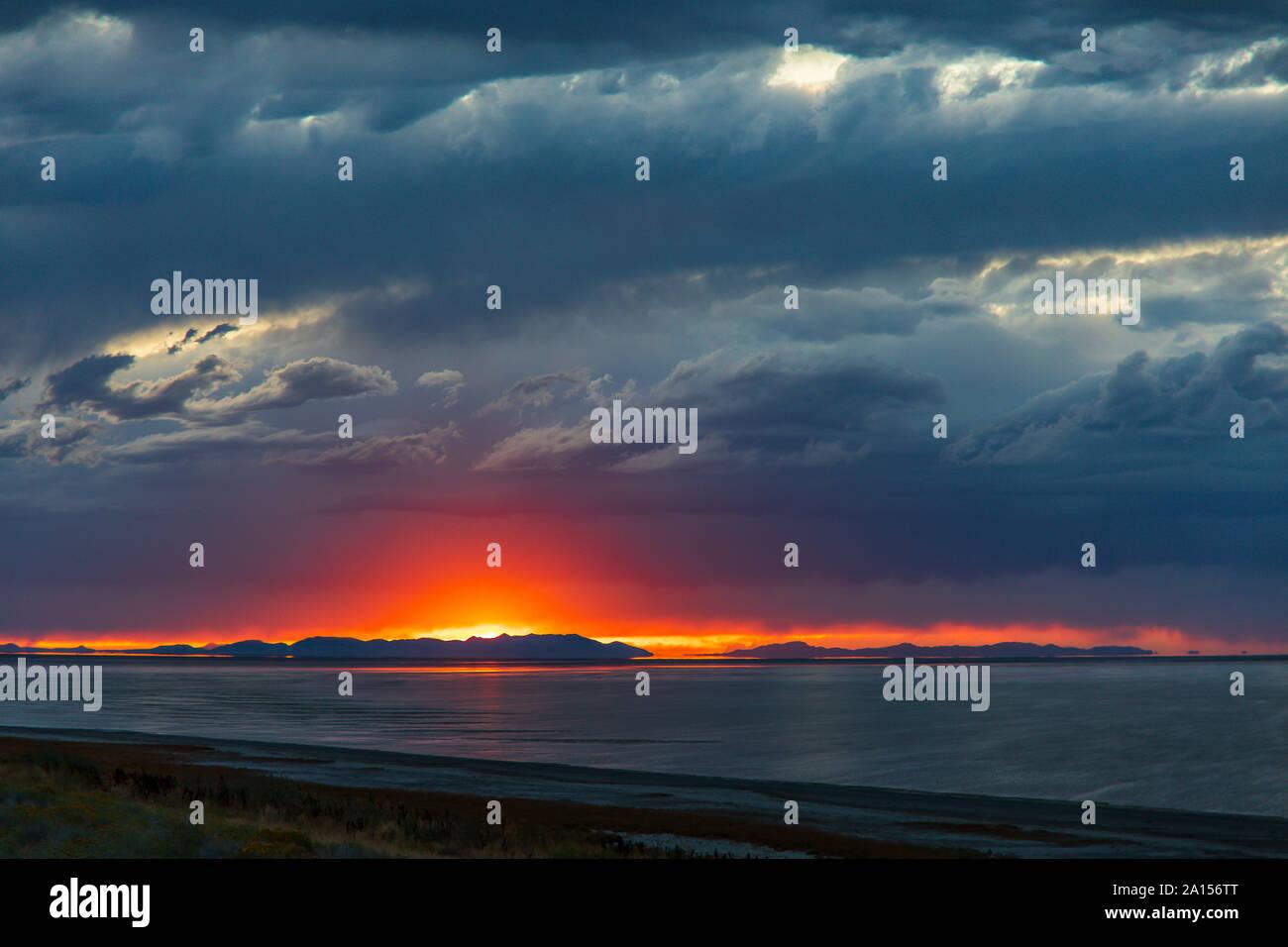 En esta foto el sol sobre las montañas de Lakeside lanza un resplandor en las amenazadoras nubes encima y reflexionando sobre el Gran Lago Salado. Foto de stock