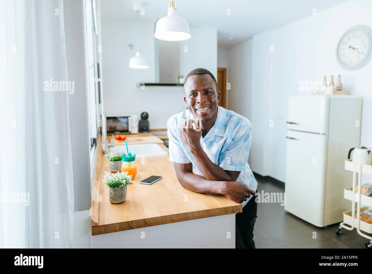 Retrato del joven sonriente en la cocina de casa Foto de stock