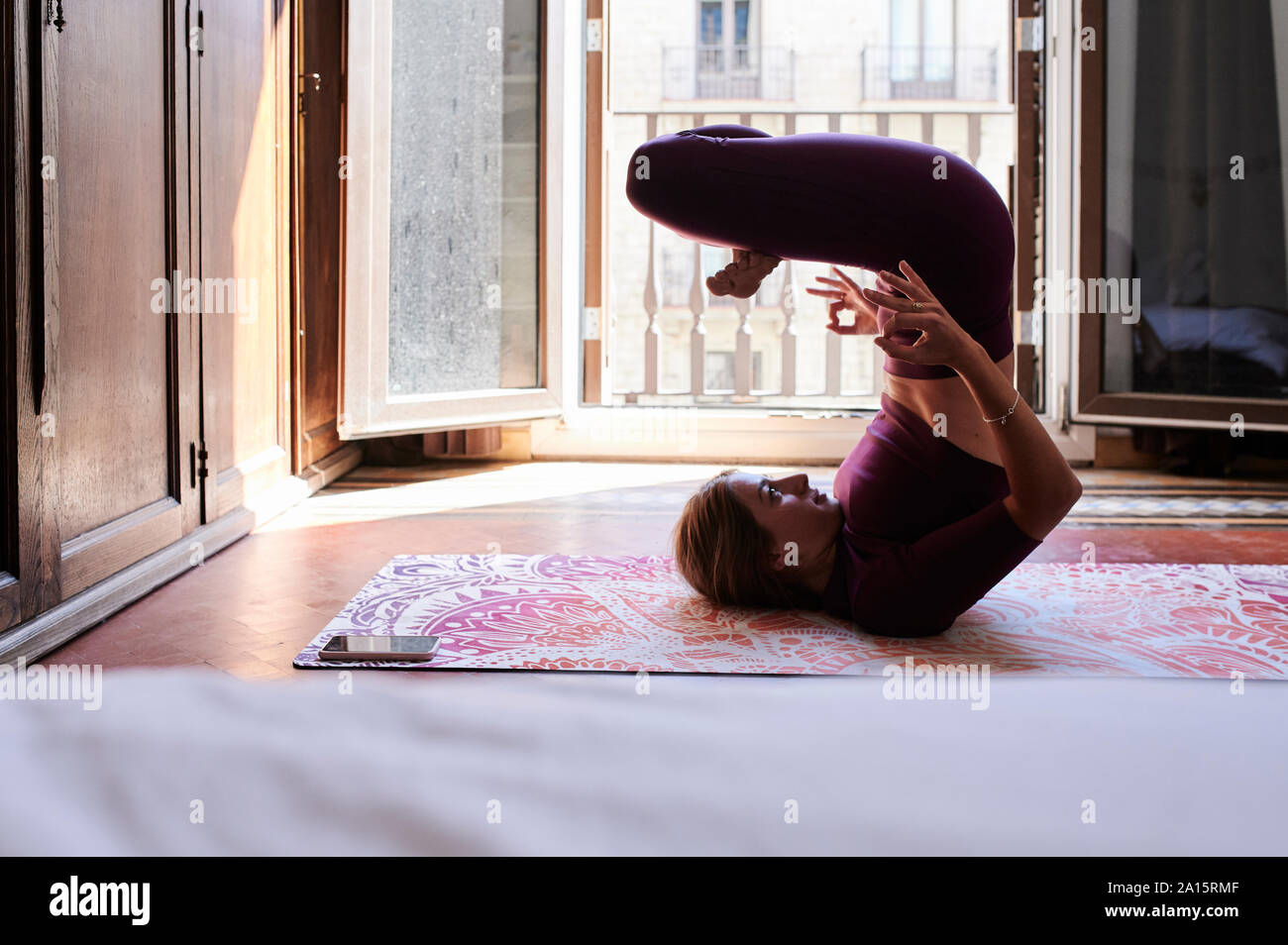 Mujer joven morenita practicando yoga en la residencia de estudiantes Foto de stock